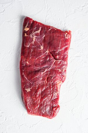 Raw skirt or flank steak,on a white stone background top view vertical.