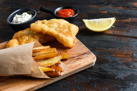 Fish and chips in a paper cone on wood chopping board dip and lemon - fried cod, french fries, lemon slices, tartar sauce, ketchup tomatoe and with mushy peas served in the Pub or Restaurant over old wooden planks dark table side view close up space for text.