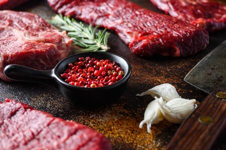 Side view Close up on red pepper near machete Steak, Flank steak, cut near denver alternative beef steak and a cleaver butcher meat knife a rustic metall background. Foto de archivo