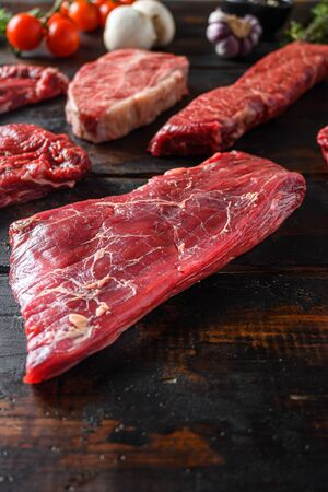 Alternative Flank bavette or flap steak beef t steak near tri-tip and top blade oyster cuts close up in front of other cuts in butchery on old wood table side view vertical.