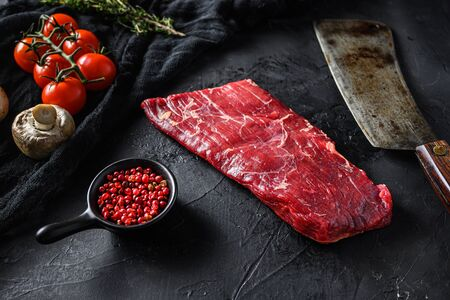 Raw, flap or flank, also known Bavette steak near butcher knife with pink pepper and rosemary. Black stone background. Side view vertical.