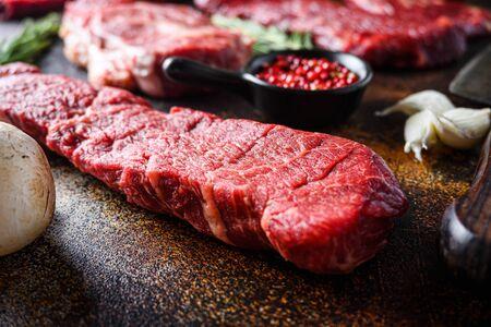Side view Close up denver Steak, Flank steak, cut near denver alternative beef steak and a cleaver butcher meat knife a rustic metall background selective focus.