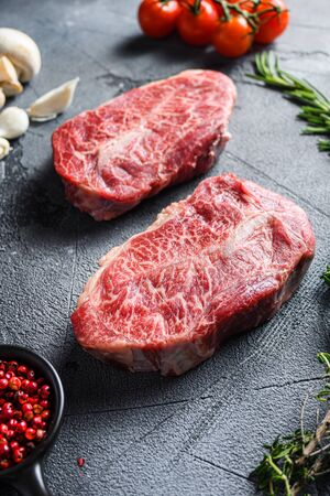 Raw top blade flat Ironcut, on black slate , bio marbled beef with herbs tomatoes peppercorns over grey stone surface background side vertical close up. Banco de Imagens