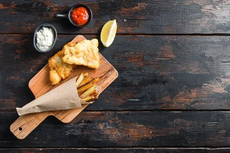 Fish and chips in a paper cone on wood chopping board dip and lemon - fried cod, french fries, lemon slices, tartar sauce, ketchup tomatoe and with mushy peas served in the Pub or Restaurant over old wooden planks dark table top view space for text or recipe