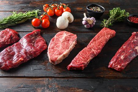 A set of different types of raw beef steaks alternative cut flap flank Steak, machete steak or skirt cut, Top blade or flat iron beef and tri tip, triangle roast with denver cut with fresh organic herbs over wood background side view space for text.