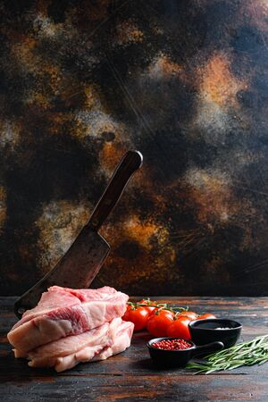Pair organic raw pork chops arranged for cooking over wooden table and rustic backdrop and chopping cleaver butcher knife, side view spacr for text vertical.