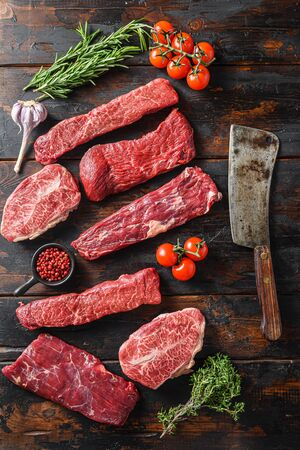 Set of flap flank Steak, machete steak or skirt cut, Top blade or flat iron beef and tri tip, triangle roast with denver cut with butcher cleaver top view over old butcher wood table.