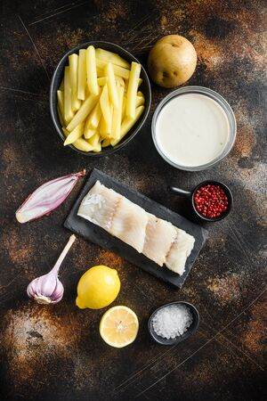 Raw cod fillet and other organic ingredients recipe fish and chips and beer batter, potatoe, shallotgarlic, salt, peppercorns on rustic metal textured surface or table top view .