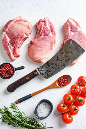 Set for bio grilling butcher cleaver over organic bio Raw pork chops , baking or frying, textured white background. vertical top view layflat.