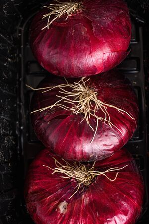 Farm red onions in tray on old oak wooden table. Close up top view. High quality.