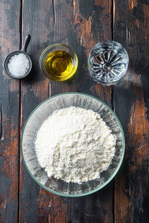 Ingredients for the dough, flour oil water and salt on wood background.