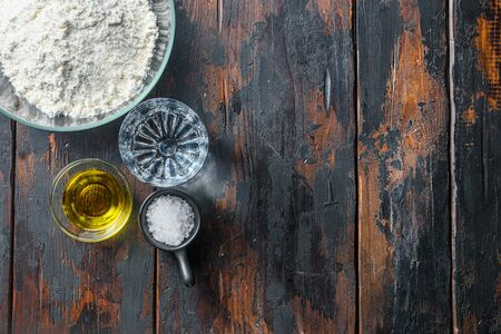 Ingredients for the dough, flour oil water and salt on wood background space for text.
