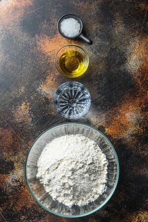 Ingredients for the dough, flour oil water and salt on darkbackground