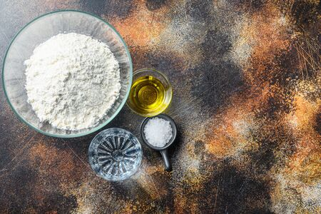Ingredients for the dough, flour oil water and salt on darkbackground space for text. Banque d'images