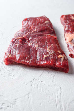 Raw Flap meat, London Broil organic meat cut side view close up over white concrete background vertical selective focus.