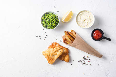 Fried fish and chips in a paper cone on white background with all components classic recipe takeaway food top view white stone textured background space for text.