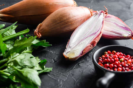 Organic shallot, eschalot or scallion raw ripe onions with greens and rose peppercorns sliced and halved black concrete textured background side view selective focus.