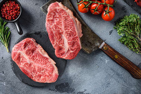 Raw top blade oyster Steak on stone and meat butcher cleaver, marbled beef with herbs tomatoes peppercorns top view.