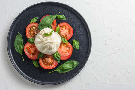 Salad with traditional italian burrata cheese made from cream and milk of buffalo or cow on black flat plate top view flatlay white concrete background space for text.