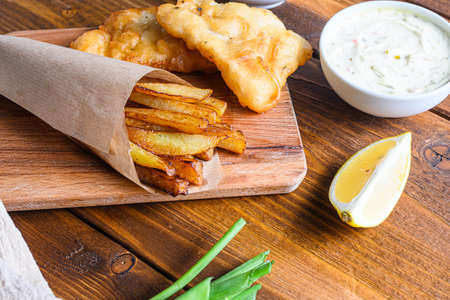 Detail of fish chips with dip and lemon, mashed minty peas, tartar sauce in paper cone on wood chopping board dip and lemon - fried cod, french fries, lemon slices, tartar sauce, ketchup tomatoe served in the Pub or over light old wooden planks table side view close selective focus.