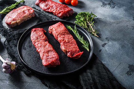 Raw denver, top blade, tri tip steak on a black plate and stone slate with seasonings, herbs gray concrete background. Side view close up selective focus new wide angle space for text.