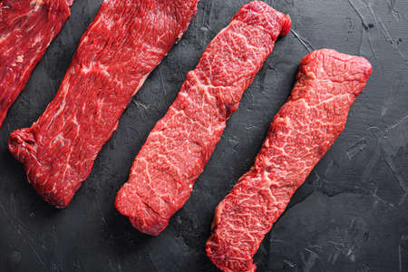 Raw, alternative beef steaks flap flank Steak, machete steak or skirt cut, Top blade or flat iron beef and tri tip, triangle roast with denver cut. Black stone background. Top view
