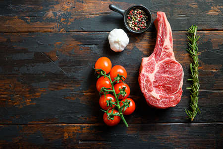 Raw uncooked black angus Bone In Steak in rustic style on wooden table background. with tomato garlic herbs and peppercorns rosemary space for text