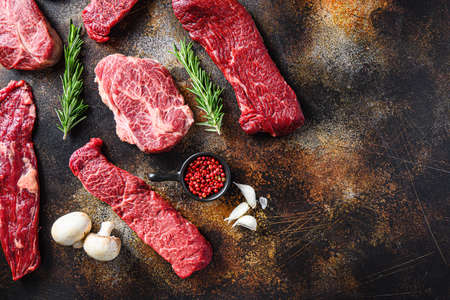 Variety, of raw beef steaks flap flank Steak, machete steak or skirt cut, Top blade or flat iron beef and tri tip, triangle roast with denver cut top view over old rustic metal surface space for text