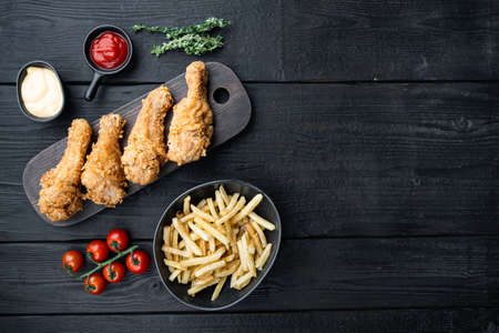 Fried crispy chicken legs, drumstick parts on black wooden background, top view, with space for text.