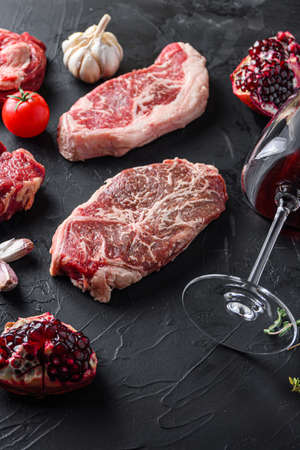 Top blade, beef steak cuts, with herbs, seasoning and red wine glass on black table, side view