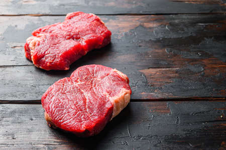 Raw rumpsteaks over dark old wooden background, side view with space for text