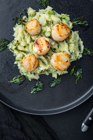 Seafood, scallops grilled with minty potatoes and pea, flat lay, on black textured background