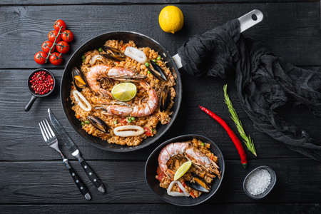 Paella on black wooden planks, top view, food photo.