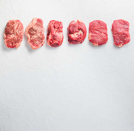 Rraw beef steaks set top blade, rump, chuck eye roll over white concrete background, top view space for text
