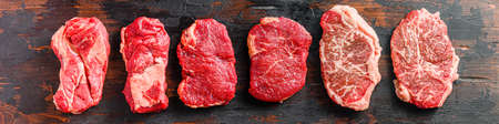 A set of different types of raw beef steaks: top blade, rump, chuck eye roll over old wooden background top view banner size