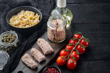 Delicious lumaconi pasta meal with tuna and baby capers, on black wooden table with copy space for text Stock Photo