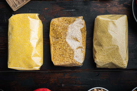 Couscous, bulgur and polenta in pounch, top view on dark wooden background.