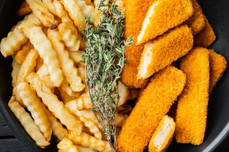 Fried Fish Sticks with French Fries. Fish Fingers. British fish and chips, fried potato, on frying iron pan, top view flat lay