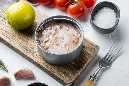 Canned italian tuna set, on wooden cutting board, on white background with herbs and ingredients