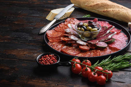 Antipasto platter cold meat with chorizo, fuet, salami, salchichon and longaniza on dark wooden background with space for text.