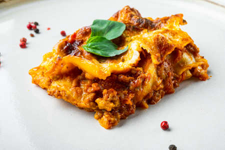 Classic meat lasagna with cheese Bechamel and Bolognese sauce set, on plate, on white stone background
