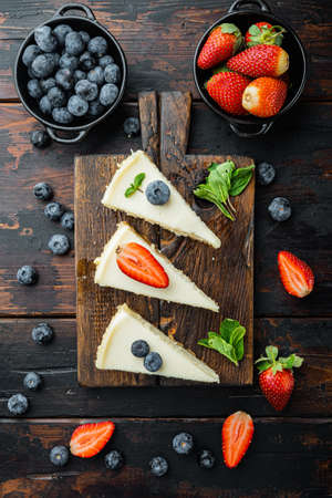 Classic New York Cheesecake, sliced, on old dark wooden table background, top view flat lay