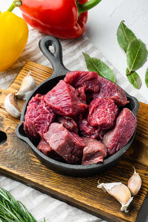 Beef stew prepared for goulash cooking set with sweet bell pepper, in cast iron frying pan, on white stone surface