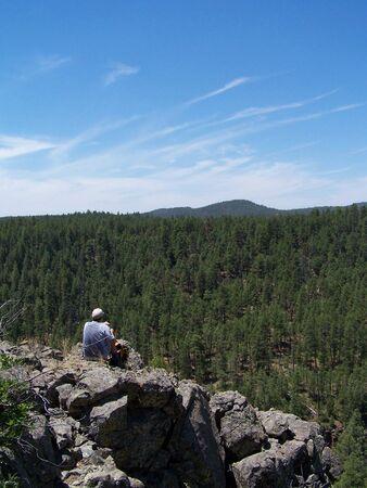 man sitting on rock at canyon