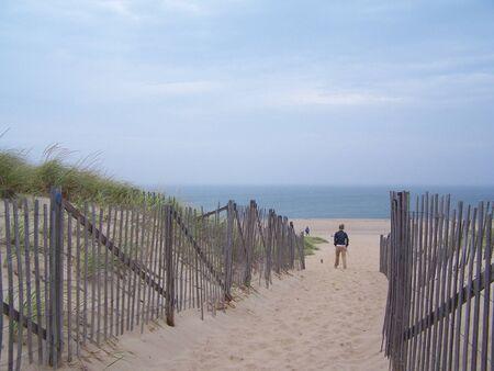 girl on beach, picket fence Stock Photo