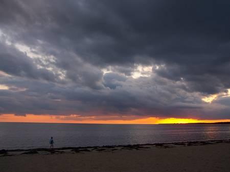 sunset on beach woman walking Stock Photo