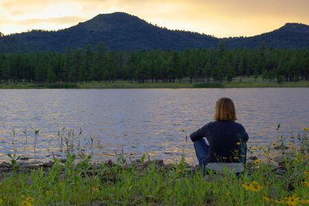Girl sitting by lake at sunset