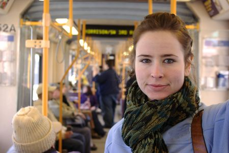 Girl with green scarf and blue fleece in train Stock Photo