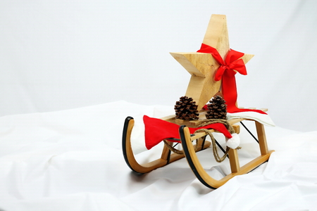 Christmas star decoration with red bow on a sledge