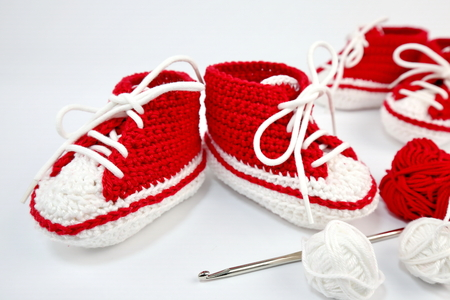 self-crocheted baby shoes made of cotton. Isolated on white background